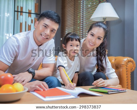 Father man mother helping their children to do their homework in their living room - stock photo