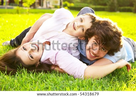 father, mother and child lying on grass - stock photo