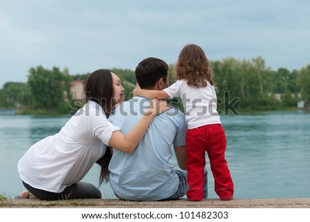 Father, mother and daughter - family on the river bank - stock photo