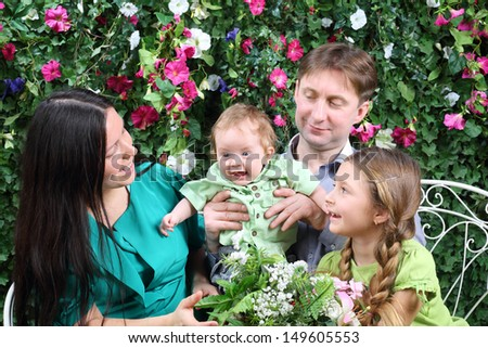 Father, mother and sister look at baby on bench in garden near verdant hedge. - stock photo