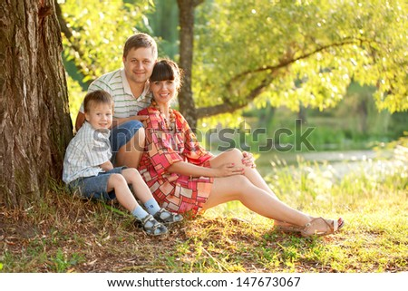 Father, mother and son in the park. Summer holiday. Happy family outdoors. Healthy lifestyles concept. - stock photo