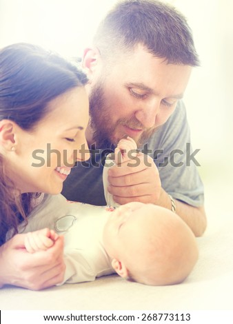 Father, Mother and their Newborn Baby. Happy Family - Mom, Dad and Baby kissing and hugging. Resting in bed together. Parenthood concept.  - stock photo