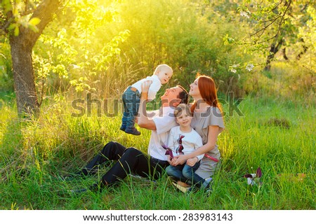 Father, mother and two sons are playing in the garden on sunset - stock photo