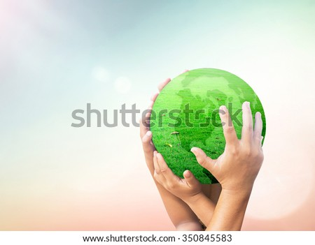 Father, mother, son hands holding green globe of grass on blurred beautiful nature background. Synergies Ecology World Environment Day CSR Mission International Human Solidarity Cancer medical concept - stock photo