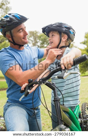 Father on a bike with his son on a sunny day - stock photo