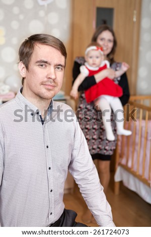 Father on foreground with mother holding baby on background - stock photo