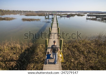 father or grandfather and son or grandson walking down dock with crab trap - stock photo