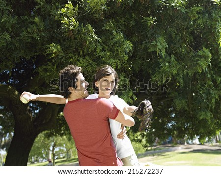 Father picking up and embracing son (10-12) in park, boy holding baseball bat and glove, smiling - stock photo