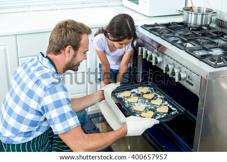 Father placing cookies tray in oven while daughter looking beside him - stock photo