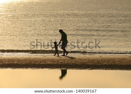father play with son on beach - stock photo