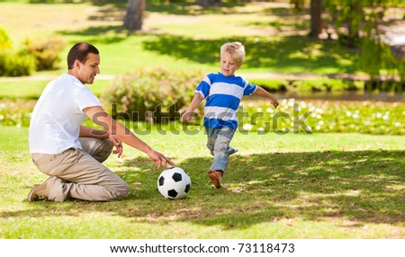 Father playing football with his son - stock photo