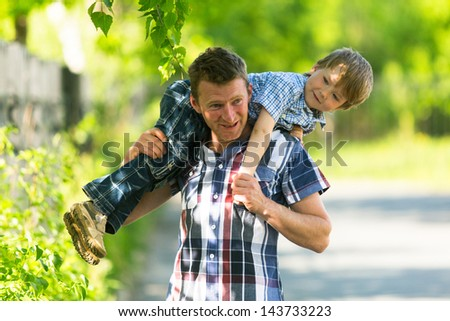 Father playing in the grass with his small son - stock photo