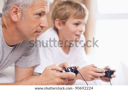 Father playing video games with his young son in a bedroom - stock photo