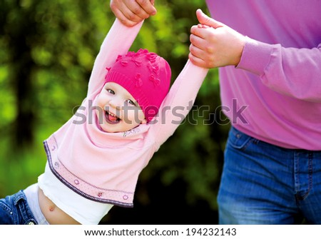 father playing with a daughter in the park, lifting her up by the arms - stock photo