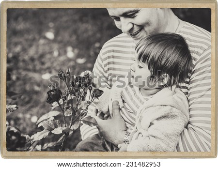 father playing with baby on nature black and white vintage card - stock photo