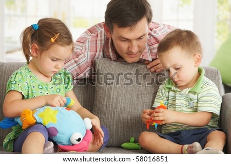 Father playing with children having fun on sofa at home.? - stock photo