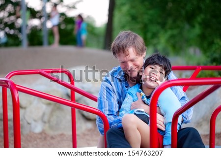 Father playing with disabled son on merry go round at playground. Child has cerebral palsy.  - stock photo