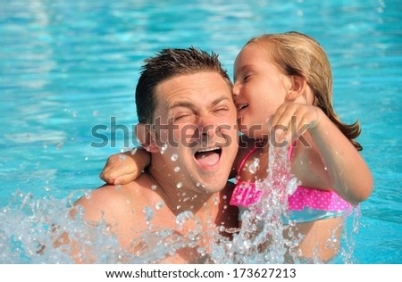 Father playing with his daughter in pool. - stock photo
