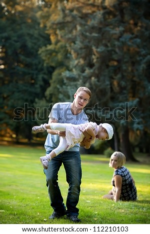 Father playing with his family in the park - stock photo