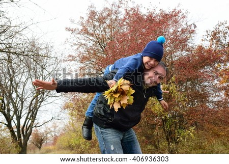 Father playing with his son in the autumn forest - stock photo