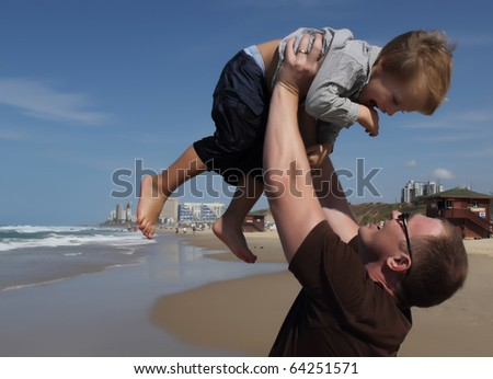 Father playing with his son on the beach - stock photo