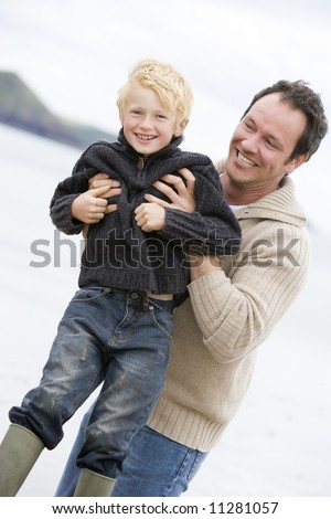 Father playing with son at beach - stock photo