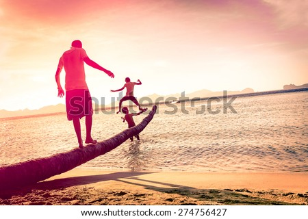 Father playing with sons at tropical beach with tilted horizon - Concept of  family union with man and children having fun together - Modified unrecognizable silhouettes - Marsala filtered color tones - stock photo