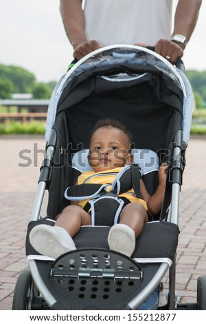 Father Push Little African American Baby Boy in Stroller Outdoor - stock photo