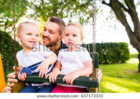 Father pushing his daughters on swing in a park. - stock photo
