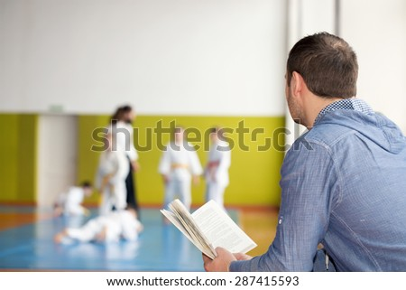 Father reading a book while waiting for his kids training martial arts - stock photo