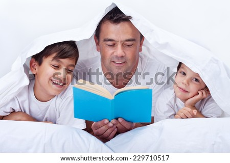 Father reading a story to his little sons - family time together - stock photo