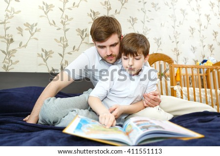 Father reading geographic book together with son on bed in child room. Looking in book - stock photo