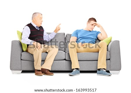 Father reprimending his son seated on a couch isolated on white background - stock photo
