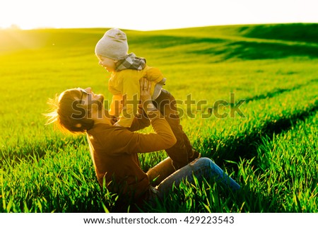 Father resting with his young son on summer field at sunset - stock photo