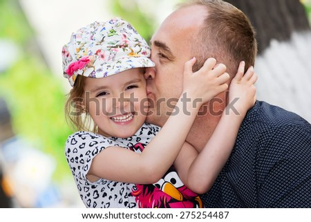 Father's day. Dad kissing his daughter.Happy smiling child with parent. Family portrait. - stock photo