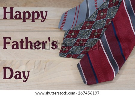 Father's day message on white card on arrangement of red and gray neckties laying on a wooden surface. The ties are all color coordinated. The necktie is a common gift to give to Dad on Father's Day - stock photo