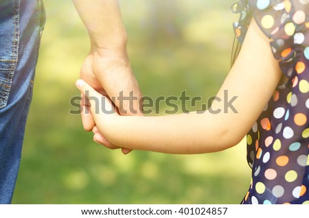 Father's hand lead his child daughter outdoors, trust family concept - stock photo