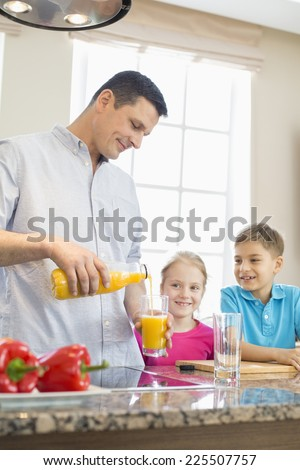 Father serving orange juice for children in kitchen - stock photo