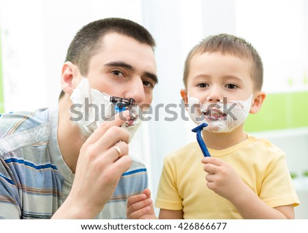 Father shaving in the mirror. Kid son imitates father - stock photo