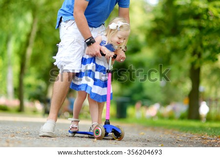 Father showing his adorable little daughter how to ride a scooter in a summer park - stock photo