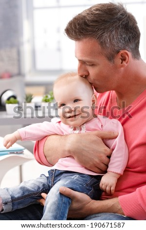 Father sitting holding on lap baby daughter, kissing smiling baby's head. - stock photo
