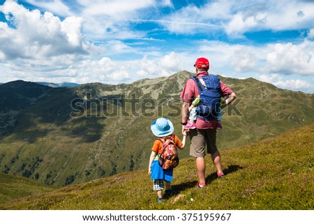 father,son and baby in carrier watching mountain view while hiking in the austrian summer alps - stock photo