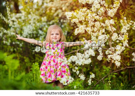 father, son and daughter in the lush garden near apple trees and cherry trees in the rays of the setting sun - stock photo
