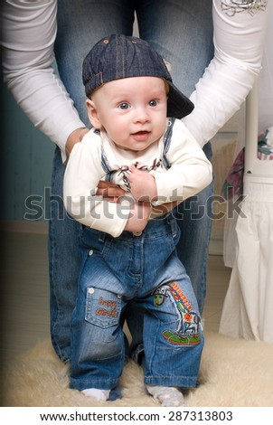 Father suppoted son. First babies steps with father. - stock photo