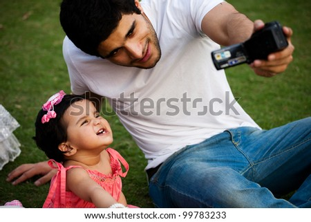 father taking a self portrait with his daughter on digital camera, biracial family - stock photo