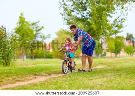 father teaches son to ride the bicycle - stock photo
