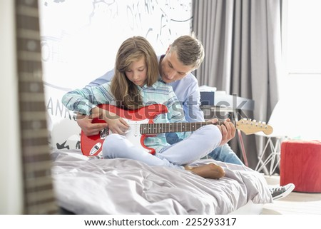 Father teaching daughter to play guitar at home - stock photo