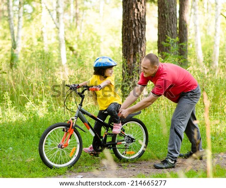 father teaching his daughter to ride a bike - stock photo