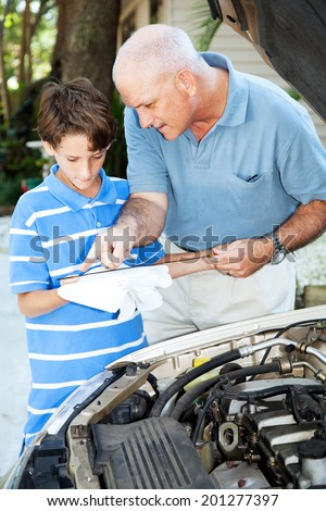Father teaching his son how to check the oil on the family car.   - stock photo