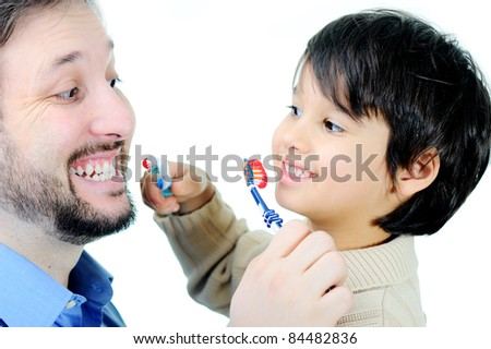 Father teaching his son how to clean teeth - stock photo